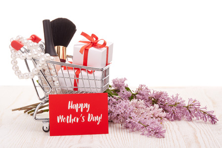 Shopping trolley with gift boxes and brenches of Lilac on a wooden table on white background. Greeting card. Mothers day. Stock Photo