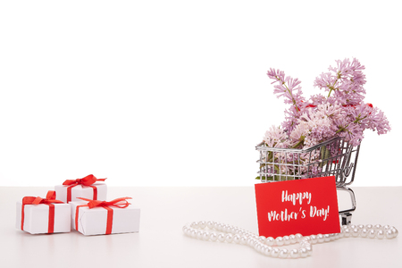 Shopping trolley with brenches of Lilac, pearl beads and gift boxes  on white background. Copy space for adding your content.  Advertising. Greeting card. Mothers day. Banco de Imagens