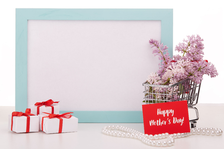 Shopping trolley with brenches of Lilac, pearl beads, gift boxes and frame with blank space on white background. Copy space for adding your content.  Advertising. Greeting card. Mothers day. Banco de Imagens