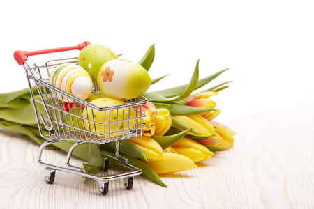 Colored easter eggs in shopping trolley and spring tulips flowers lying on a wooden table on a white background.