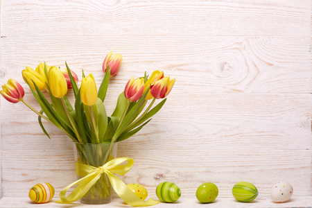 Colored easter eggs, spring tulips flowers in the vase  and ribbon on wooden background. Greeting card.