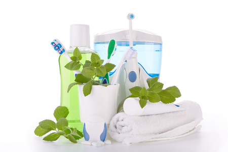 Toothbrushes, toothpaste, oral irrigator, floss, rinse, gums and fresh leaves of mint on a white background. Accessories for cleaning of teeth. Oral hygiene. Daily dental care. Reklamní fotografie