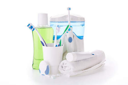 Toothbrushes, toothpaste, oral irrigator, floss, rinse, gums and fresh leaves of mint on a white background. Accessories for cleaning of teeth. Oral hygiene. Daily dental care. Standard-Bild