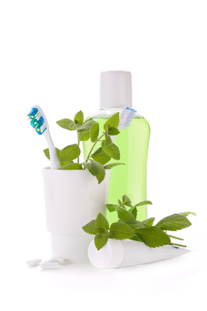 Toothbrushes, toothpaste, rinse, gums and fresh leaves of mint on a white background.  Accessories for cleaning of teeth. Oral hygiene. Daily dental care.