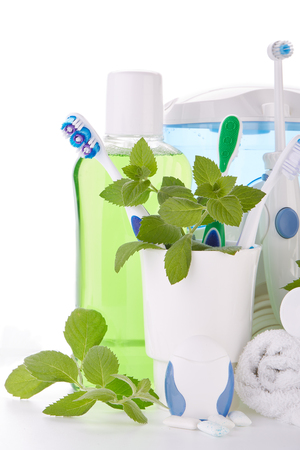 Toothbrushes, toothpaste, oral irrigator, floss, rinse, gums and fresh leaves of mint on a white background. Accessories for cleaning of teeth. Oral hygiene. Daily dental care. Stock Photo