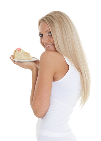 Young happy woman with delicious cake stands on a white background.