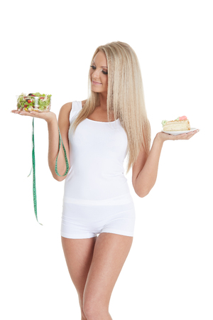 Young beautiful woman holds bowl of salad with fresh vegetables, piece of cake and tape for measuring on a white background.  Concept of healthy food.