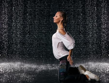 Het mooie meisje dat in water onder regen op een zwarte achtergrond danst. Moderne dansen.