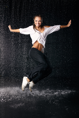 The beautiful girl dancing in water under rain on a black background.  Modern dances.