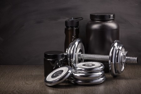 Sports nutrition (supplements), and dumbbells on a black background. Fitness, bodybuilding, sport and healthy lifestyle concept.