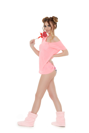 Cheerful young woman stands with lollipop on a white background. Pin up style. Imagens