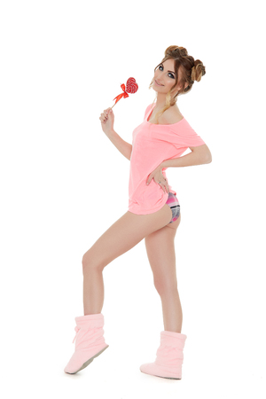 Cheerful young woman stands with lollipop on a white background. Pin up style. Фото со стока