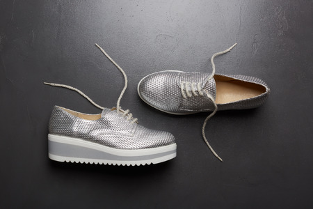 Fashion shoes, new modern silvery sneakers on grey background.
