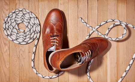 Fashion shoes, new brown polished classic shoes for men and rope lies on a wooden background. Top view.