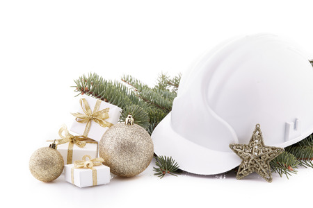 Construction hard hat, fir tree branches and Christmas decoration isolated on a white background. New Year and Christmas. Stock Photo