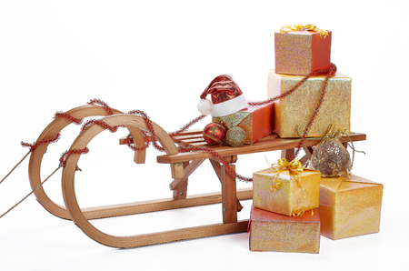 Wooden sledge with gift boxes and Christmas decoration isolated on a white background. Christmas and New Year.
