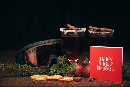 Mulled wine, fir branches, ski glasses and  christmas decoration on a wooden table on a dark background. Winter vacation. Stock Photo