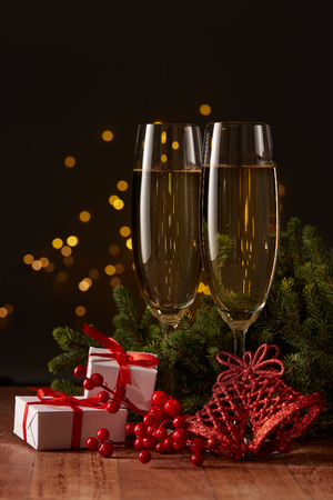 Two glasses with champange, gift boxes, fir tree branch with decorations on a dark background with LED lights garland. New year and Christmas. Stockfoto