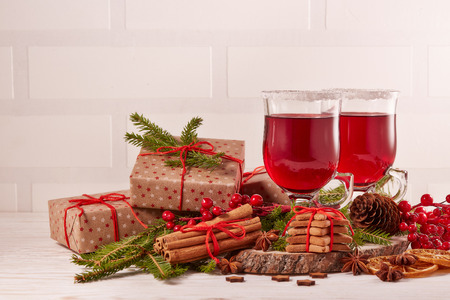 Still life with glasses of mulled wine or fruit tea, gift boxes, gingerbread cookies and christmas decorations on a wooden table.  Christmas and New Year treat.
