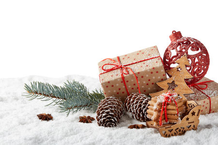 Fir tree branch, decorations, gingerbread cookies and gift boxes on a winter snow background with copy space.  New Year and Christmas
