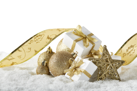 Christmas still life with golden balls, tape, star and gift boxes lying on  winter snow on a white background with copy space. New Year and Christmas. Greeting card