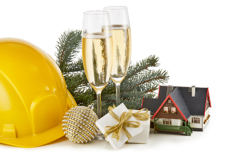 Construction hard hat, fir tree branches, model house,  two glasses with champange and Christmas ornament isolated on a white background. New Year and Christmas. Horizontal view