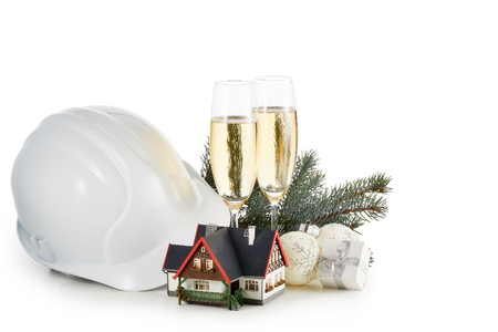 Construction hard hat, fir tree branches, model house,  two glasses with champange and Christmas ornament isolated on a white background. Horizontal view with clipping path. New Year and Christmas.