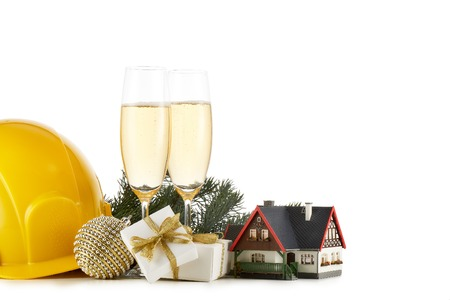 Construction hard hat, fir tree branches, model house,  two glasses with champange and Christmas ornament isolated on a white background. New Year and Christmas. Horizontal view with copy space