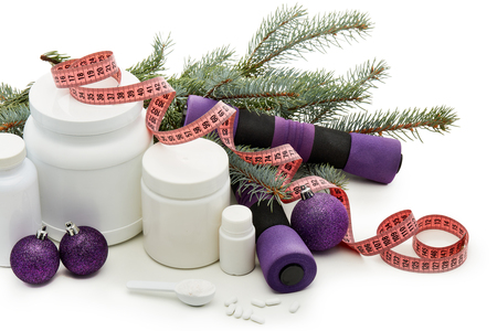 Sports nutrition (supplements), dumbbells, fir tree branches and christmas ormament on a white background.  Horizontal view. New Year and Christmas. Fitness. Healthy lifestyle. Stock Photo