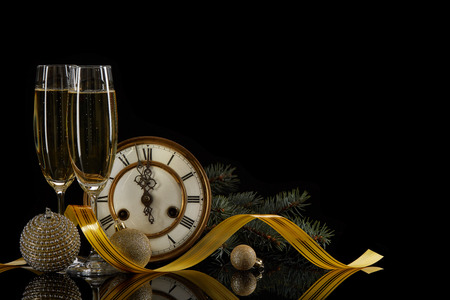 Two wineglasses with champange, fir tree branches,  clock and christmas ornament on a black background with reflection. Copy space. Christmas and New Year background