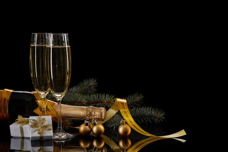 Two wineglasses with champange, bottle, gift box and serpentine on a black background with reflection. Copy space. Christmas and New Year background