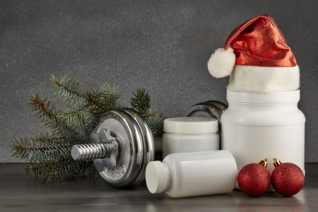 Sports nutrition (supplements), dumbbells, fir tree branches and christmas ormament on a dark background.  Horizontal view. New Year and Christmas. Fitness. Healthy lifestyle. Standard-Bild