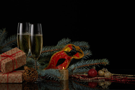 Still life with two wineglasses with champagne, gift boxes, fir tree branches and Christmas decorations  on a black background. Copy space. New Year and Christmas
