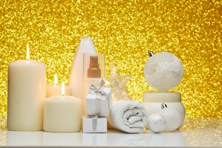 Spa still life with cosmetic creams, candles, towel, gift boxes and Christmas ornaments on a gold background. New Year and Christmas Healthy lifestyle, body care, Spa treatment and relaxation concept