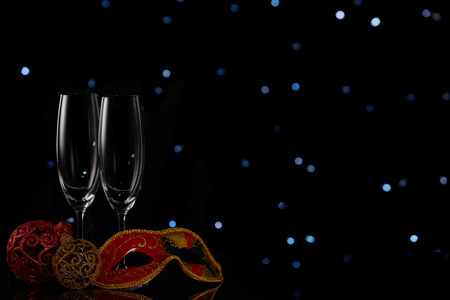 Two wineglasses with champagne and Christmas decorations  on a black background with LED lights garland. Copy space. New Year and Christmas