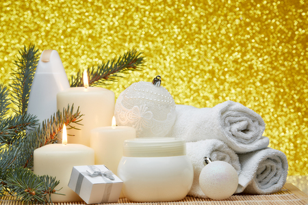 Spa still life with cosmetic creams, candles, fir branches, gift boxes and Christmas ornaments on a gold background. Healthy lifestyle, body care, Spa treatment and relaxation concept.