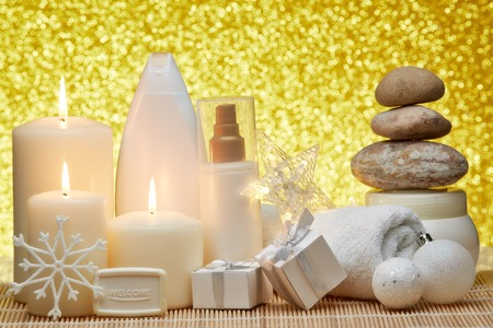 Spa still life with cosmetic creams, candles, towel, gift boxes and Christmas ornaments on a gold background. Healthy lifestyle, body care, Spa treatment and relaxation concept. Stock Photo