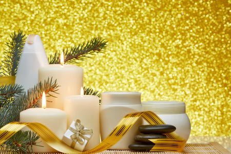 Spa still life with cosmetic creams, candles, fir branches, black stones, gift box and Christmas ornaments on a gold background.Healthy lifestyle, body care, Spa treatment and relaxation concept.