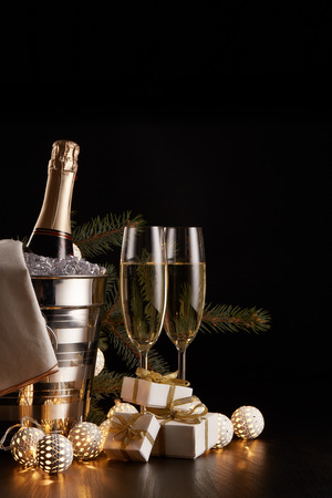 Still life with champagne bottle standing in a bucket with ice, two full champagne flutes, LED lights garland  and Christmas ornaments on a black background. Christmas and New Year celebration