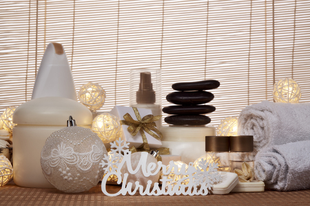 Spa still life with cosmetic creams,  towel, black stones, gift boxes and Christmas ornaments standing on bamboo mat. Christmas Healthy lifestyle, body care, Spa treatment and relaxation concept Stock Photo