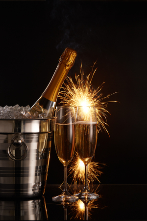 Still life with cooled champagne bottle standing in a bucket with ice, two full champagne flutes and sparklers (fireworks) on a black background with reflection. New Year, Christmas, Events Imagens