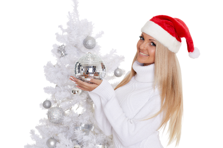 Young woman in Santa Claus cap  with mirror ball stands near Christmas tree on a white background.