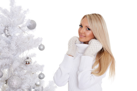 Young happy beautiful  woman in winter clothes stands near Christmas tree on a white background.