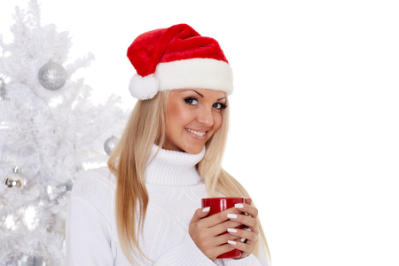 Young woman in Santa Claus cap  with red cup stands near Christmas tree on a white background.