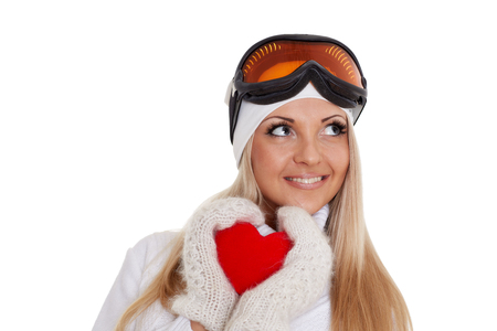 Young woman in winter clothes and ski glasses holds in hands a red heart on a white background.