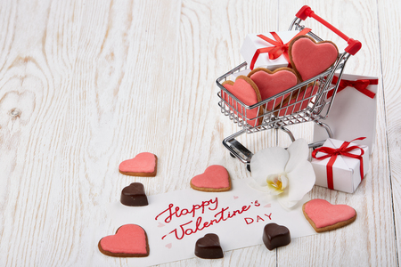 Shopping trolley with gift boxes, red heart, cookies, flower and greeting card  on a light wooden background with copy space. Valentines day,
