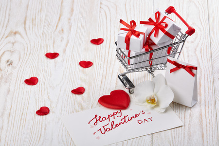 Shopping trolley with gift boxes, red heart, flower and greeting card  on a light wooden  background with copy space. Valentines day, Stock Photo