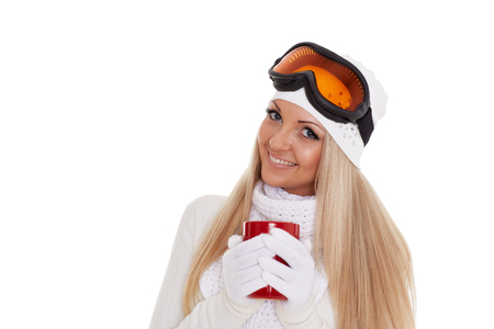 Young woman  in ski glasses  and  winter warm clothes  with red cup stands on a white background. Winter sports.