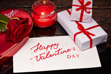 Still life with gift boxes, rose and  greeting card lying on a black background with reflection. Valentine's Day card.
