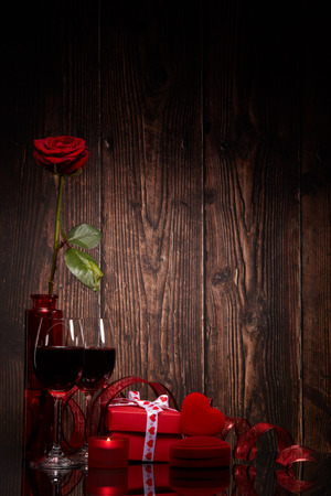Still life with rose, red heart, gift box and two glasses with wine on a wooden background. Valentine's Day card with copy space. Design element for romantic greeting card, wedding invitation,